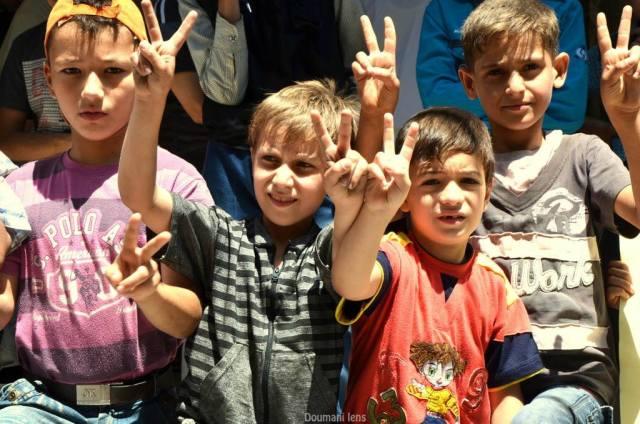 Des enfants lèvent le V de victoire à Douma